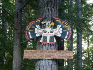 Thunderbird carving by Willard Joe placed above a notice of forest protection by senior shíshálh elders
